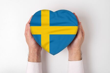 Flag of Sweden on a heart shaped box in a male hands. White background