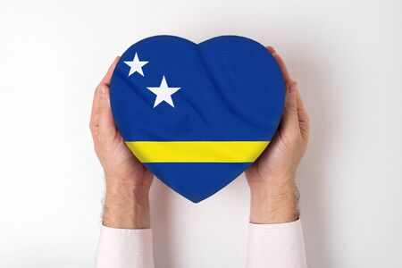 Flag of Curacao on a heart shaped box in a male hands. White background