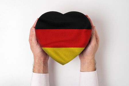 Flag of Germany on a heart shaped box in a male hands. White background