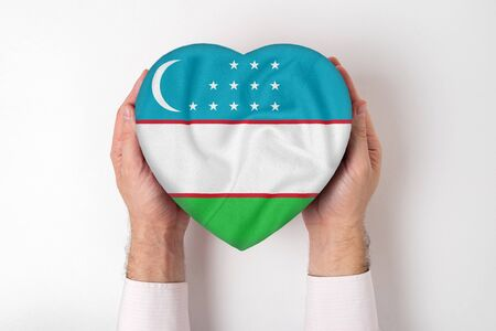 Flag of Uzbekistan on a heart shaped box in a male hands. White background