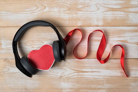Heart shape box, headphones, and ribbon on wooden background. Listen to your heart concept. Top view.