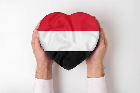 Flag of Yemen on a heart shaped box in a male hands. White background Imagens