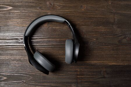 Black wireless earphones on a dark wooden background. Stereo headphones. Top view. Imagens
