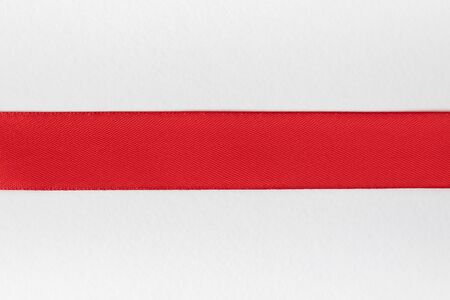 Horizontal red ribbon on a white background. Blank for designer. Top view. Close-up. Imagens