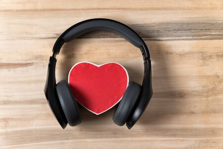 Full-size wireless headphones pulled over small red heart-shaped box on a light brown wooden table. Love music concept. Directly above.