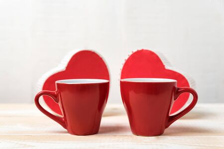 Two red cups and heart shaped boxes. Date, Valentines Day.