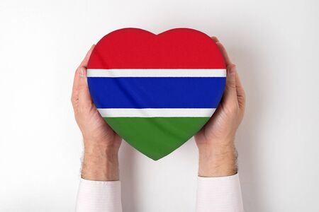 Flag of Gambia on a heart shaped box in a male hands. White background