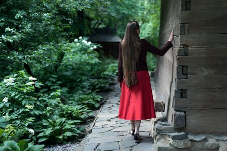 Woman with long hair in the village. Girl walks in the park. Back view. Imagens