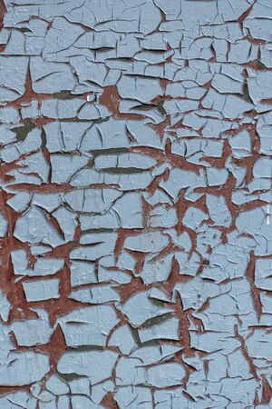 Blue board with cracks from the paint. Old wall background. Texture and background, vertical frame. Imagens