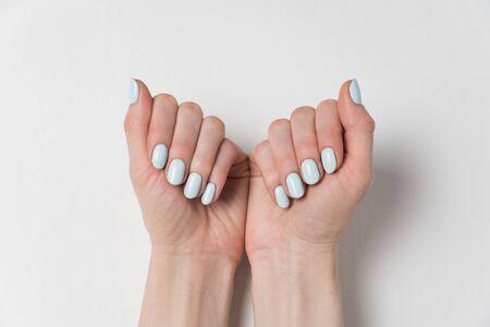 Gentle feminine manicure, blue gel polish. Hands on white background Imagens
