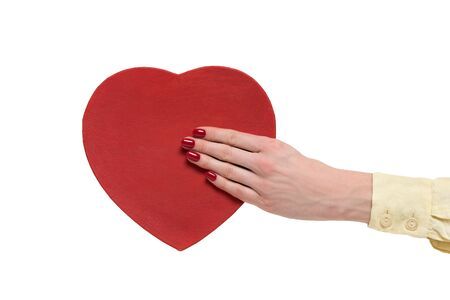 Vintage style red heart shaped box on female hand isolated on white background. Front view.