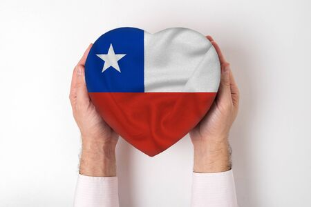 Flag of Chile on a heart shaped box in a male hands. White background