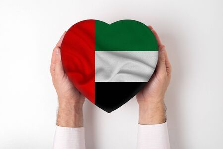Flag of United Arab Emirates on a heart shaped box in a male hands. White background