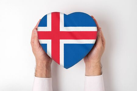 Flag of Iceland on a heart shaped box in a male hands. White background