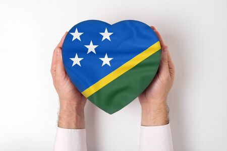 Flag of Solomon Islands on a heart shaped box in a male hands. White background Imagens