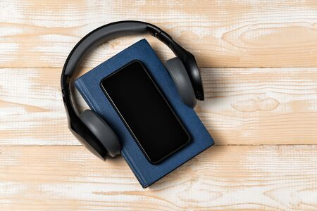 Book, headphones and phone on wooden background. Listen to audiobooks concept