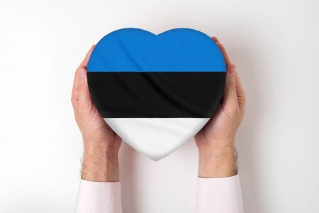 Flag of Estonia on a heart shaped box in a male hands. White background