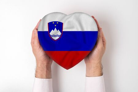 Flag of Slovenia on a heart shaped box in a male hands. White background