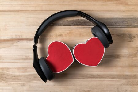Wireless headphones and two heart shaped boxes on wooden background. Music of hearts. Directly above