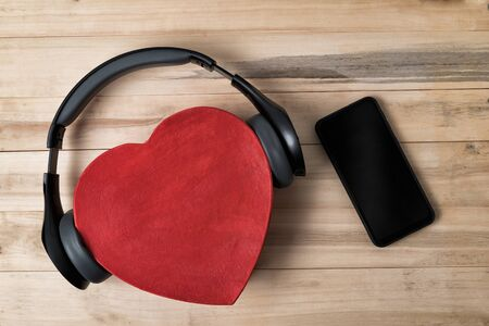Full-size wireless headphones pulled over red heart-shaped box and smartphone on light brown wooden table. Directly above.