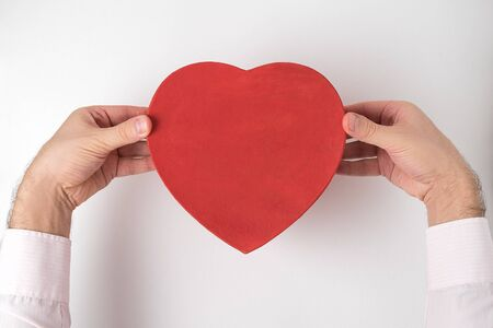 Vintage style red heart shaped box in male hands isolated on white background. Gift for Valentines day Imagens