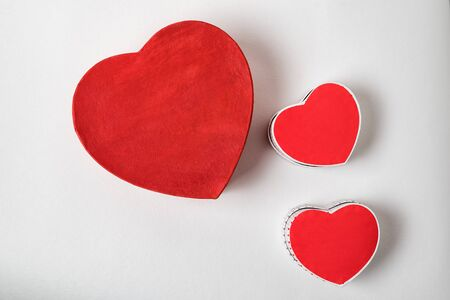 Big and two small red heart shaped boxes on table. Above view. Valentines Day