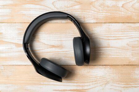 Headphones on light wooden background. Black earphones. Top view.