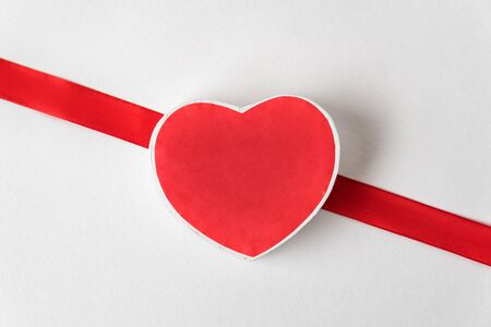 Red box in the shape of a heart on a white background. Red ribbon. Symbol of love, valentines day