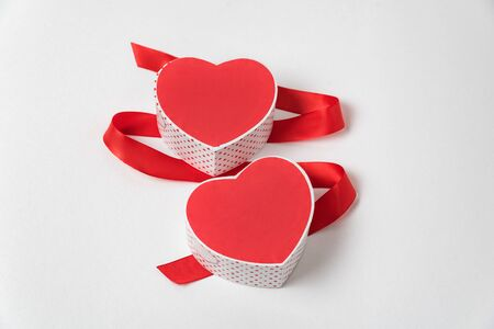 Two red heart-shaped boxes and satin ribbon on a white background. Symbol of love, Valentines Day. Imagens