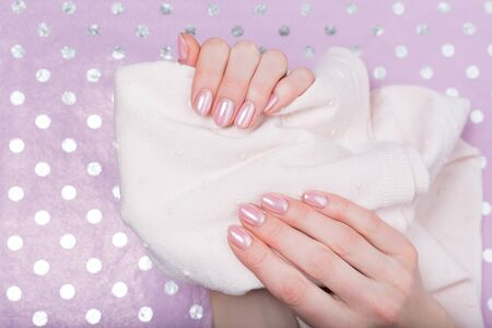 Hands with manicure. Delicate pink nail polish. Care for hands. Close-up. Imagens