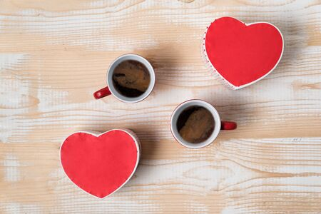 Two red cups of coffee and heart shaped boxes. Date, Valentines Day. Top view Imagens