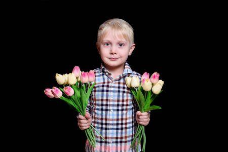 有郁金香的两花束的画象逗人喜爱的白肤金发的男孩。黑色背景