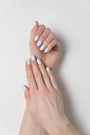 Female hands with delicate blue manicure. Gel Polish. White background. Verrical frame