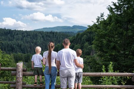 Young family with two children on nature background. Weekend with the family.