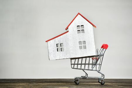 Model house and shopping cart Buying home concept. Mortgage rent