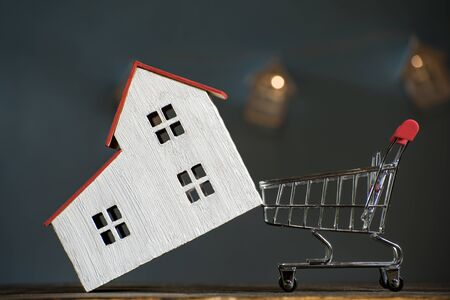 Home and shopping cart. Buying a house mortgage concept. Dark background, front view.