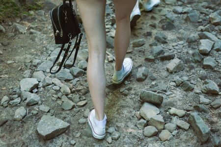 Woman legs goes on a rocky road. Hiking into the mountains. Closeup.
