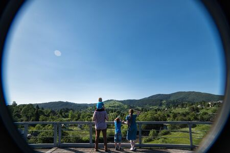 Family with children standing on the observation deck on nature background. Photo through the window. Back view. Banque d'images