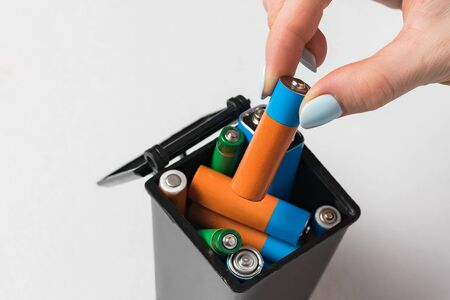 Female hand throws the used battery in the trash. Collection and recycling concept used batteries