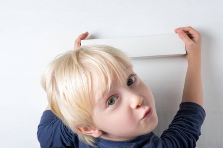 Child holds box in hands on white background. Cute little boy is happy the parcel. Top view. Stock fotó