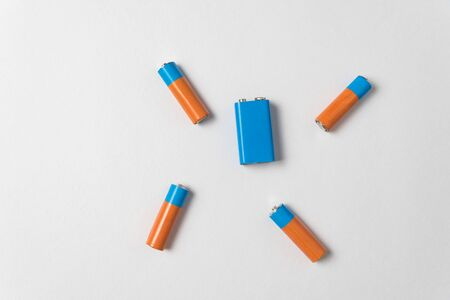 AA and PP3 batteries on white background. Batteries of different types. Top view.