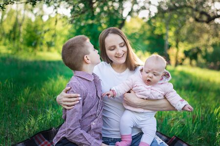 Mom on picnic with eldest son and young daughter. Motherhood and childhood concept