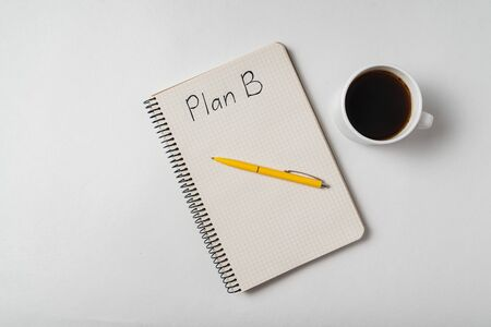 Top view of the Notepad with the words Plan B and a Cup of coffee. Backup plan ideas.