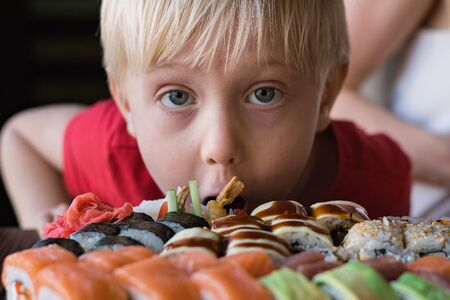 Funny fair-haired boy stares at Sushi. Child boy in cafe concept. Asian cuisine.