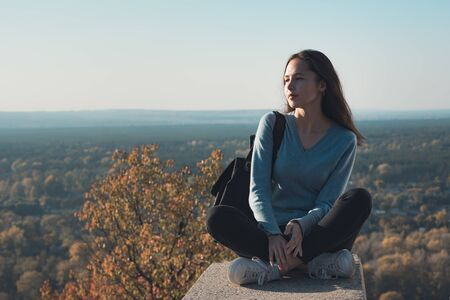 Beautiful young woman sitting on top of a hill and looks into the distance. Travel for the weekend.