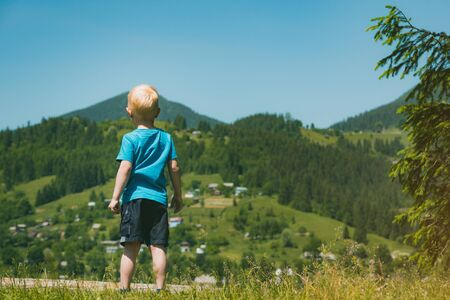 Fair-haired boy standing on mountains background. Traveling with children. Back view. Banco de Imagens