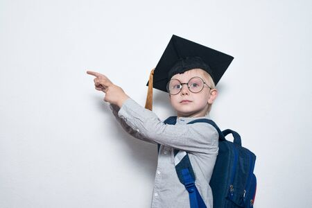Blond boy in glasses with serious look shows on board. Boy wearing student hat. Kids achievement. Copy space