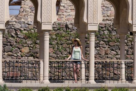 Woman stands in middle of colonnade and admiring the view. Historical sites.