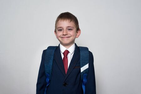 Smiling boy in school uniform and backpack on white background. Junior High School concept. half-length portrait.