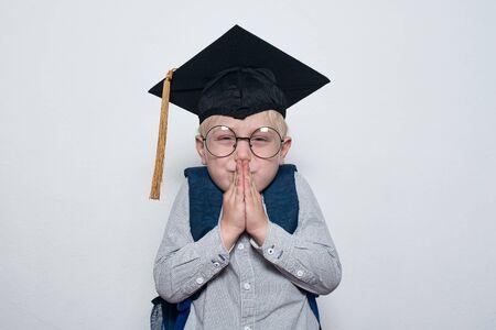 Little boy wearing in student hat. White background. Sly schoolboy plotted prank. Half-length portrait. 免版税图像